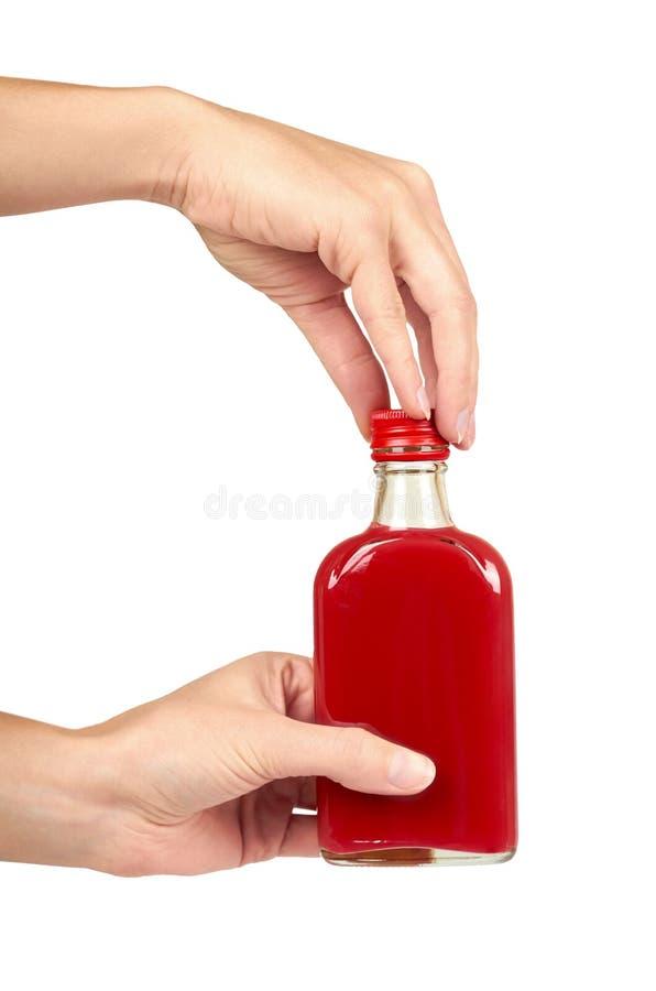 Стеклянная бутылка с красной тинктурой в руке изолированной на белой предпосылке Проблема спирта стоковые фотографии rf