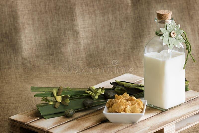 Стеклянная бутылка с парным молоком и флористическим украшением стоковые изображения rf