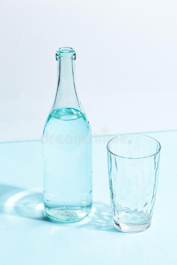 Стеклянная бутылка с чистой водой и стеклом на бело-голубой предпосылке Концепция Minimalistic творческая стоковые фото