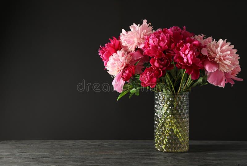 Стеклянная ваза с букетом красивых пионов на деревянном столе против черной предпосылки стоковое изображение
