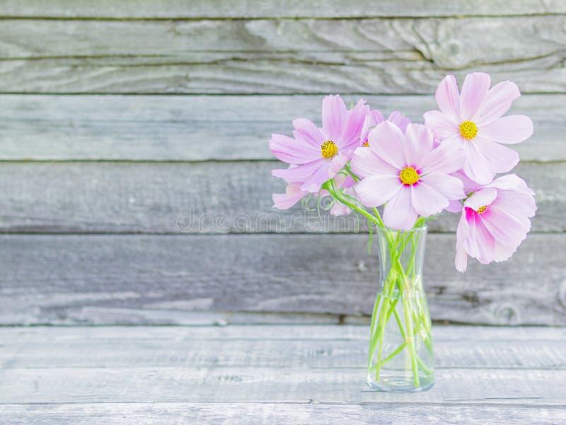 Стеклянная ваза с букетом розовых чувствительных хрупких цветков на wo стоковые фотографии rf