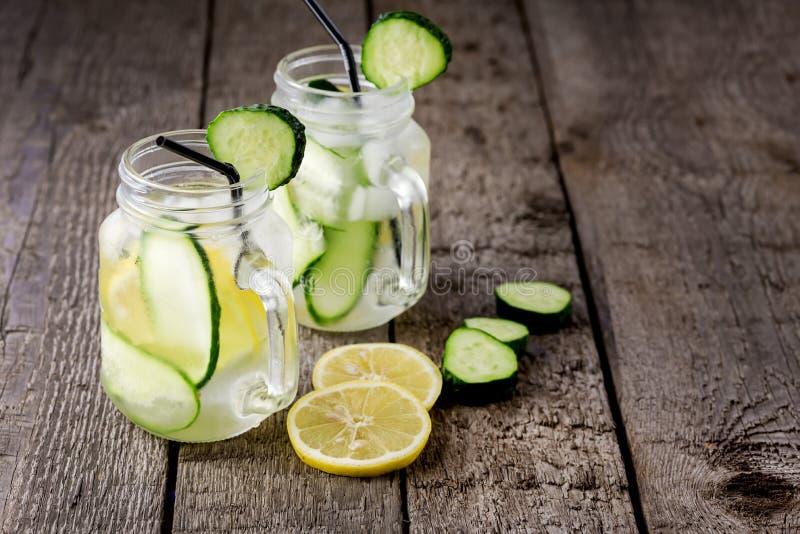 Стеклянная кружка опарника воды с лимоном и огурцом на деревянной настоянном предпосылкой напитке вытрезвителя воды стоковое фото