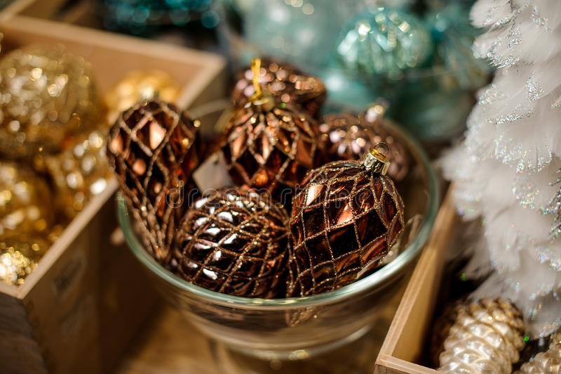 Стеклянная пластинка много блестящих темных золотых шариков игрушки различных форм стоковая фотография