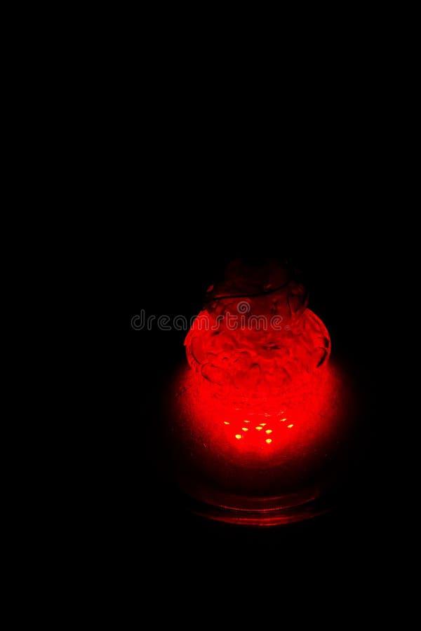 Стеклянная склянка кальяна заполненная с клокоча водой и дымом накаляет в темноте в красном цвете люминесценция в темноте r стоковое изображение