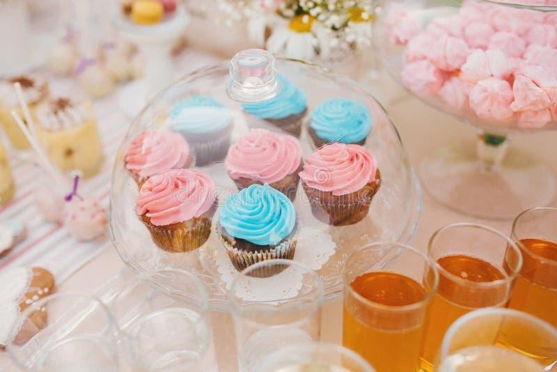 Стеклянная стойка с крышкой с розовым и голубым вкусным пирожным рядом с стеклом сока и помадок стоковая фотография rf