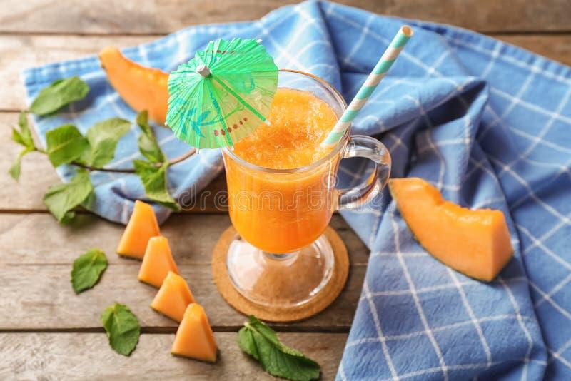 Стеклянная чашка вкусного smoothie дыни на деревянном столе стоковое фото