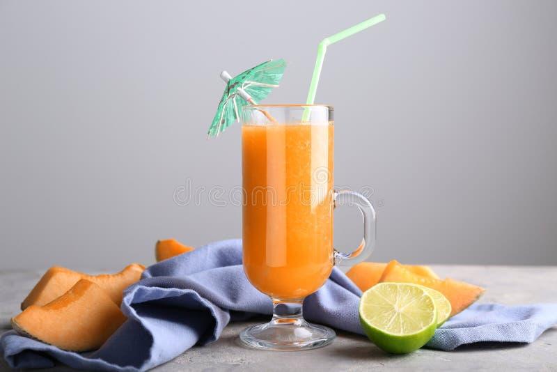 Стеклянная чашка вкусного smoothie дыни на таблице стоковое изображение