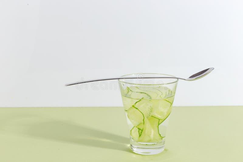 Стеклянная чашка с водой огурца на салатовой предпосылке Концепция Minimalistic творческая скопируйте космос стоковая фотография