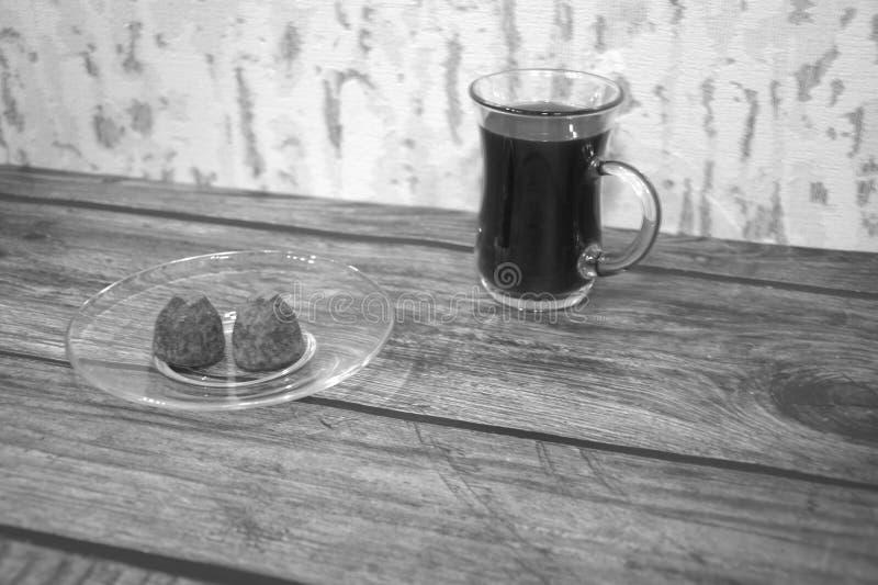 Стеклянная чашка с черным кофе и 2 шоколадами стоковое изображение