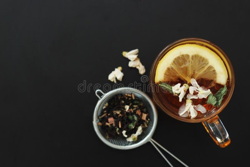 Стеклянная чашка травяного чая с акацией цветет на черной предпосылке, взгляд сверху, космосе экземпляра Холодность питья здоровь стоковые фото