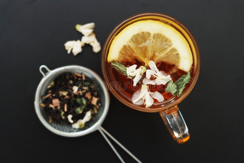 Стеклянная чашка травяного чая с акацией цветет на черной предпосылке, взгляд сверху, космосе экземпляра Холодность питья здоровь стоковые изображения