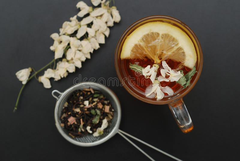 Стеклянная чашка травяного чая с акацией цветет на черной предпосылке, взгляд сверху, космосе экземпляра Холодность питья здоровь стоковое изображение rf