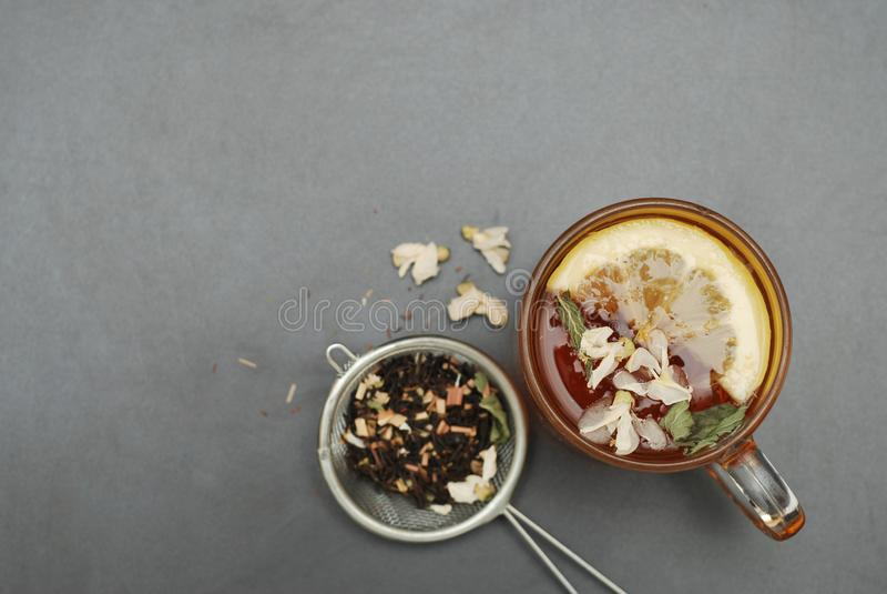 Стеклянная чашка травяного чая с цветками и медом акации на черной предпосылке, взгляд сверху, космосе экземпляра Холодность пить стоковое фото