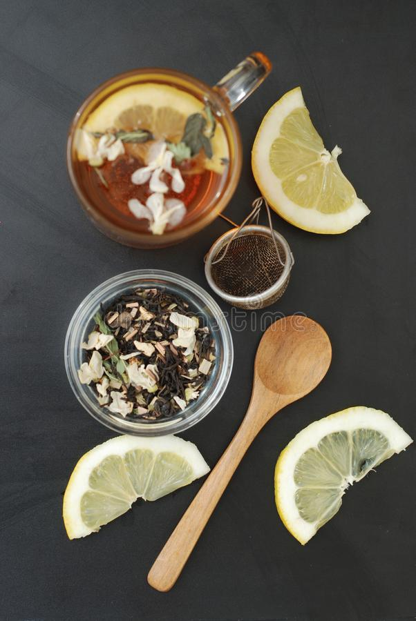 Стеклянная чашка травяного чая с цветками и медом акации на черной предпосылке, взгляд сверху, космосе экземпляра Холодность пить стоковое фото rf