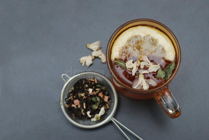 Стеклянная чашка травяного чая с цветками и медом акации на черной предпосылке, взгляд сверху, космосе экземпляра Холодность пить стоковое изображение rf
