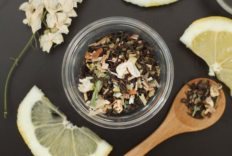 Стеклянная чашка травяного чая с цветками и медом акации на черной предпосылке, взгляд сверху, космосе экземпляра Холодность пить стоковая фотография
