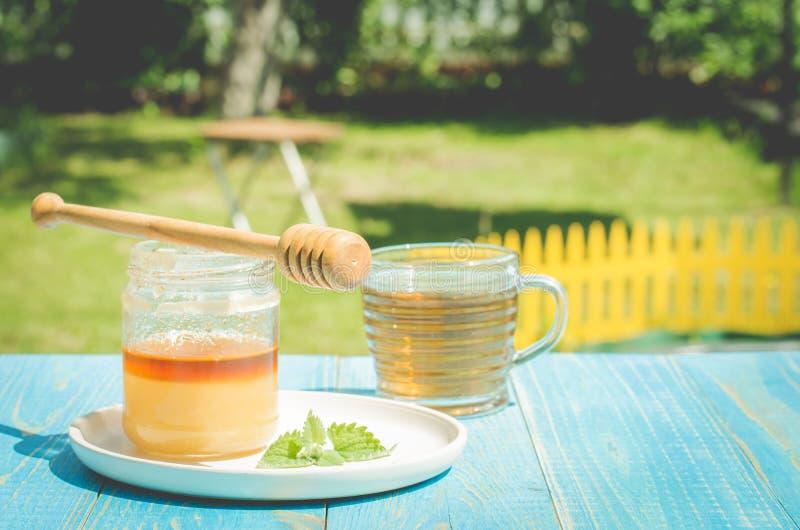 стеклянная чашка чаю с опарником меда на голубом деревянном столе в саде лета r стоковая фотография rf
