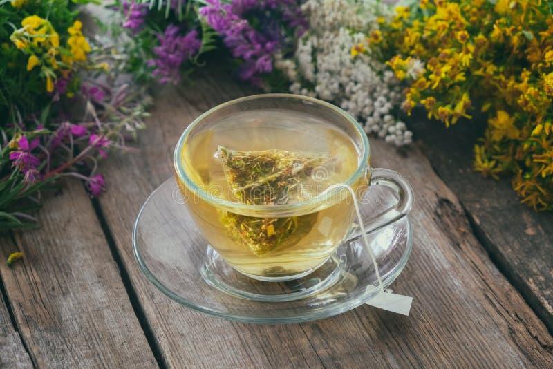 Стеклянная чашка чая с пакетиком чая здорового травяного чая и пуками целебных трав на предпосылке стоковая фотография rf