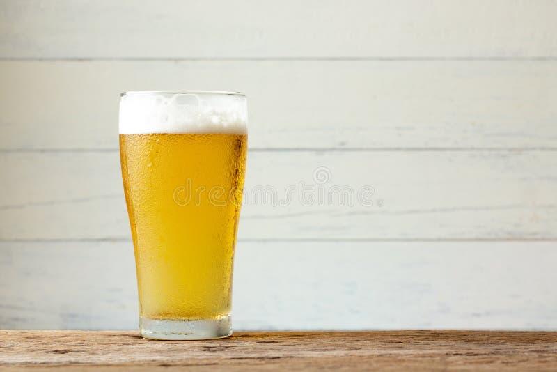 Стеклянное пиво на деревянной предпосылке с космосом экземпляра стоковые фотографии rf