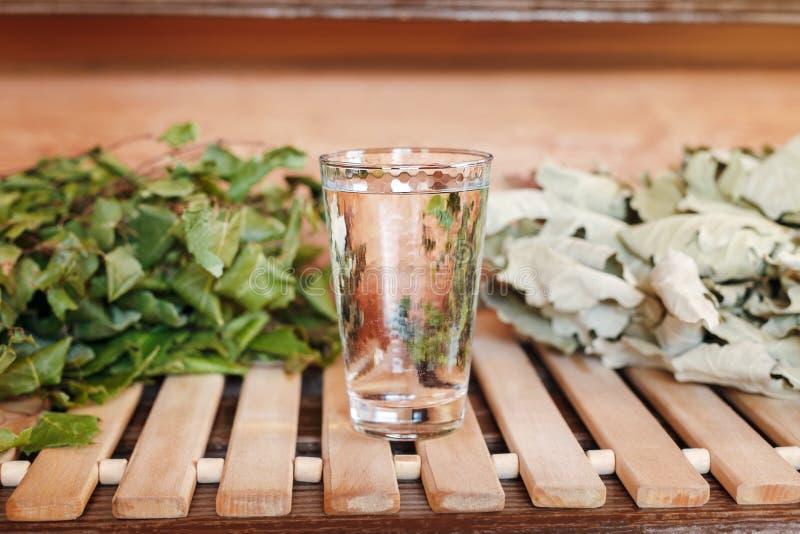 Стеклянное стекло чисто прозрачной воды в ванне около веников ванны стоковое изображение rf