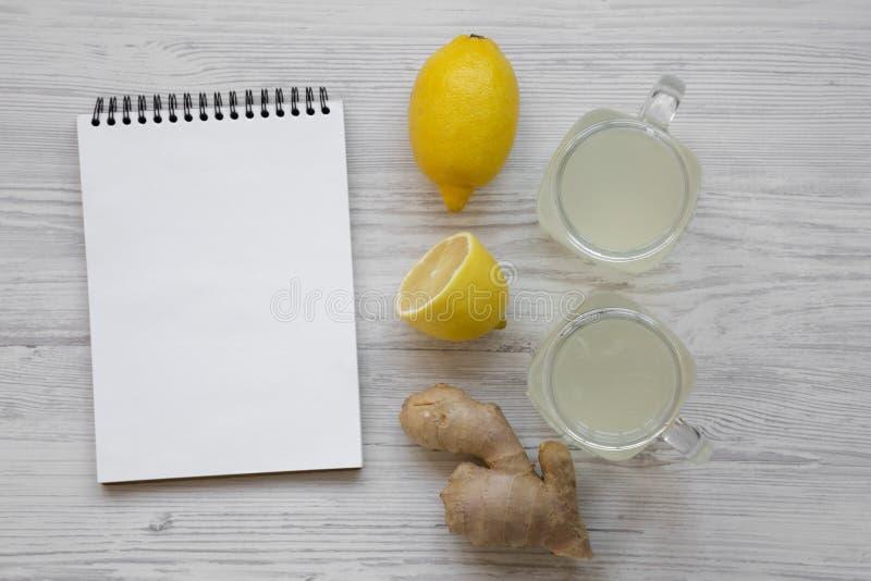 Стеклянные опарникы домодельного чая имбиря с лимоном над белой деревянной предпосылкой, взглядом сверху пустой блокнот Плоское п стоковая фотография