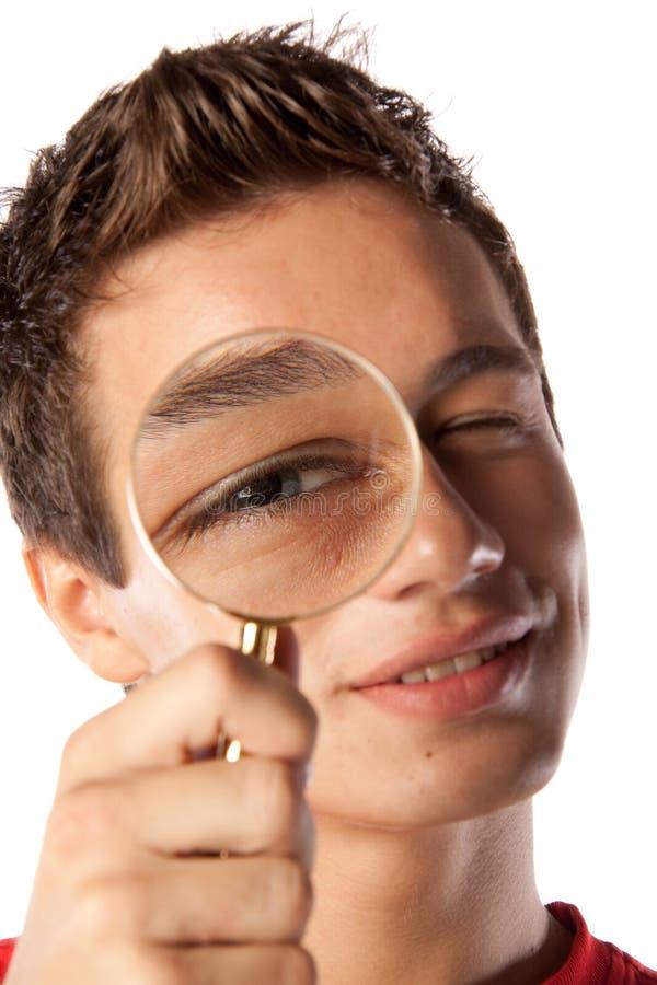 стеклянные увеличивая детеныши человека стоковое изображение