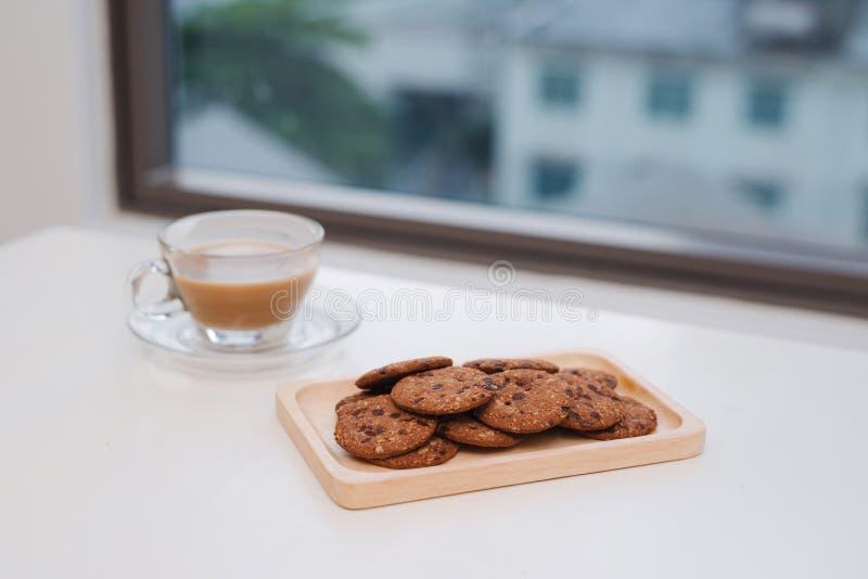 Стеклянные чашка чаю и поддонник с печеньями обломока шоколада стоковое фото rf