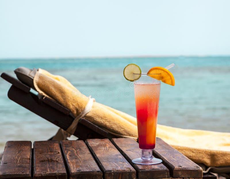 Стеклянный кубок с коктеилем на deckchair на пляже стоковые изображения rf