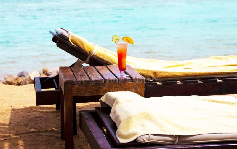 Стеклянный кубок с коктеилем на deckchair на пляже стоковое фото rf