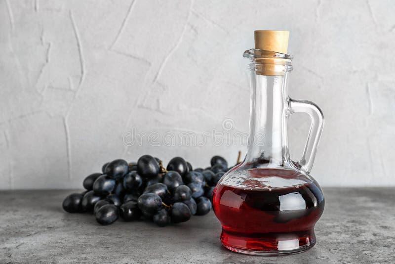 Стеклянный кувшин с уксусом вина и свежими виноградинами стоковые изображения rf