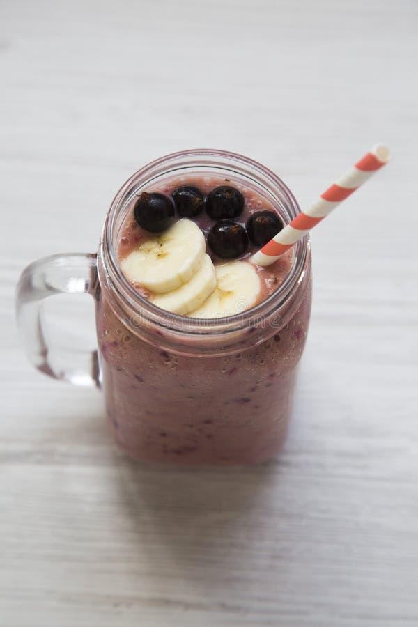 Стеклянный опарник при smoothie сделанный банана, черной смородины, молоко кокоса над белой деревянной предпосылкой, стоковое фото