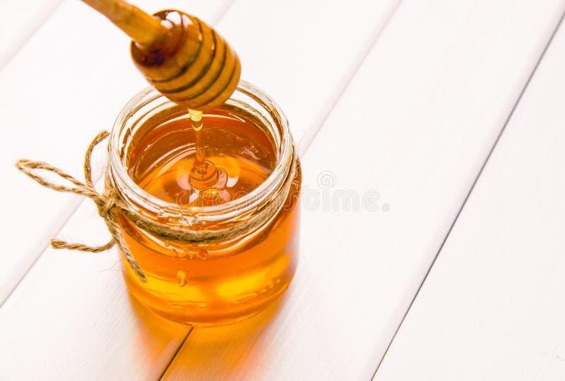 Стеклянный опарник с медом и ковшом на белой предпосылке деревянного стола стоковое фото rf