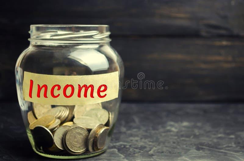 Стеклянный опарник с монетками и доходом надписи cash Распределение семейного бюджета Концепция финансов, дела и экономики A стоковое фото