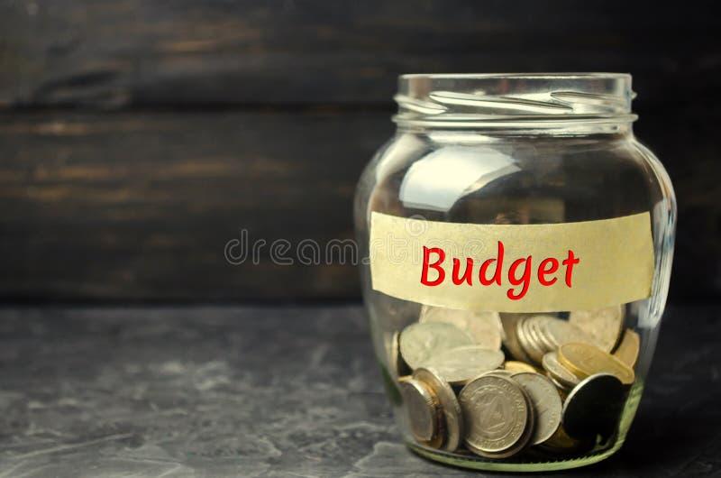 """Стеклянный опарник с монетками и надписью """"бюджет """" Концепция аккумулировать деньги в семейном бюджете Страхование семьи Distr стоковое фото"""