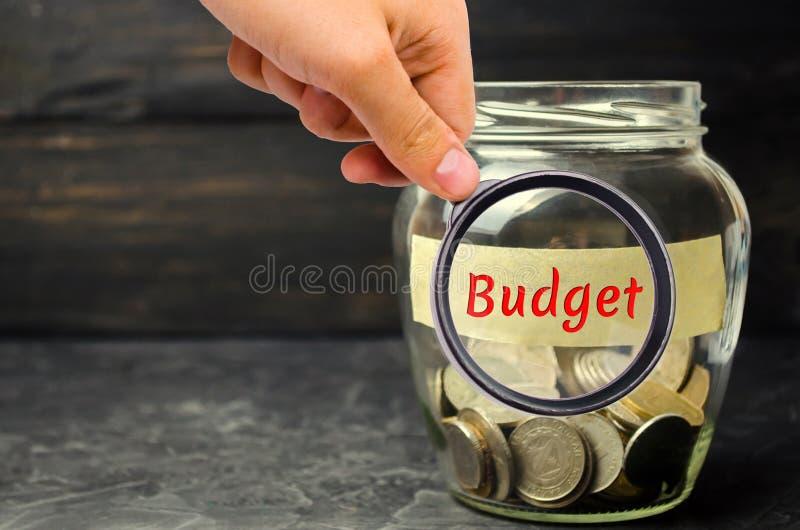 """Стеклянный опарник с монетками и надписью """"бюджет """" Концепция аккумулировать деньги в семейном бюджете Страхование семьи Distr стоковое изображение rf"""
