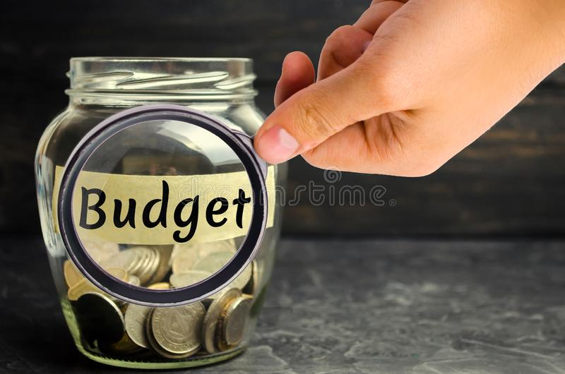 """Стеклянный опарник с монетками и надписью """"бюджет """" Концепция аккумулировать деньги в семейном бюджете Страхование семьи Distr стоковые фото"""