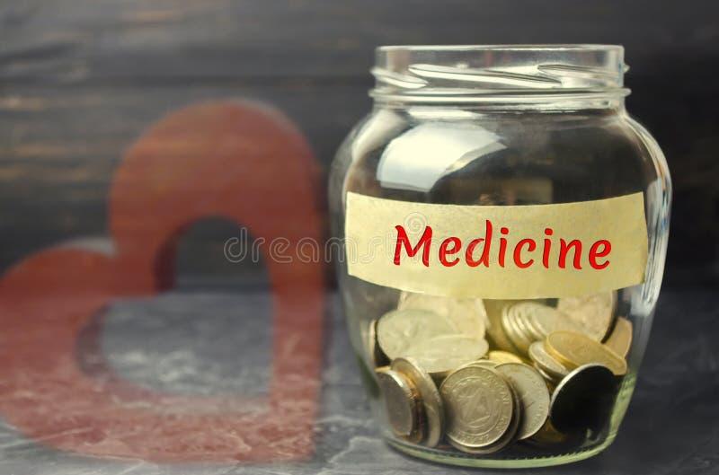 """Стеклянный опарник с монетками и надписью """"медицина """" Концепция страхования семейной медицины, здравоохранения Медицинские расход стоковые фото"""