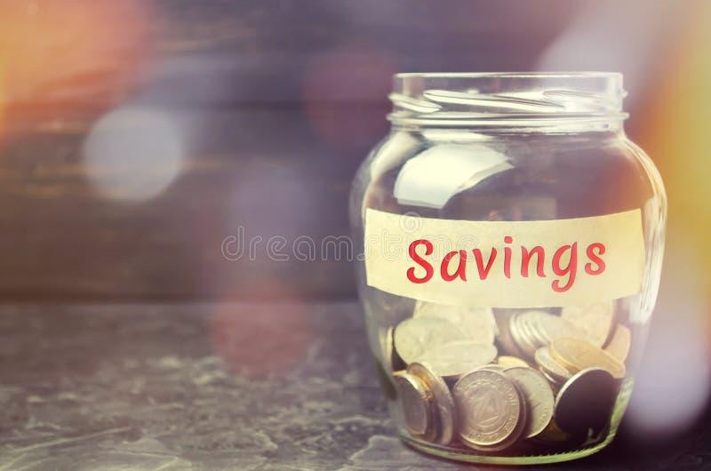 """Стеклянный опарник с монетками и надписью """"сбережения """" Концепция аккумулировать деньги в семейном бюджете Страхование семьи dist стоковая фотография"""