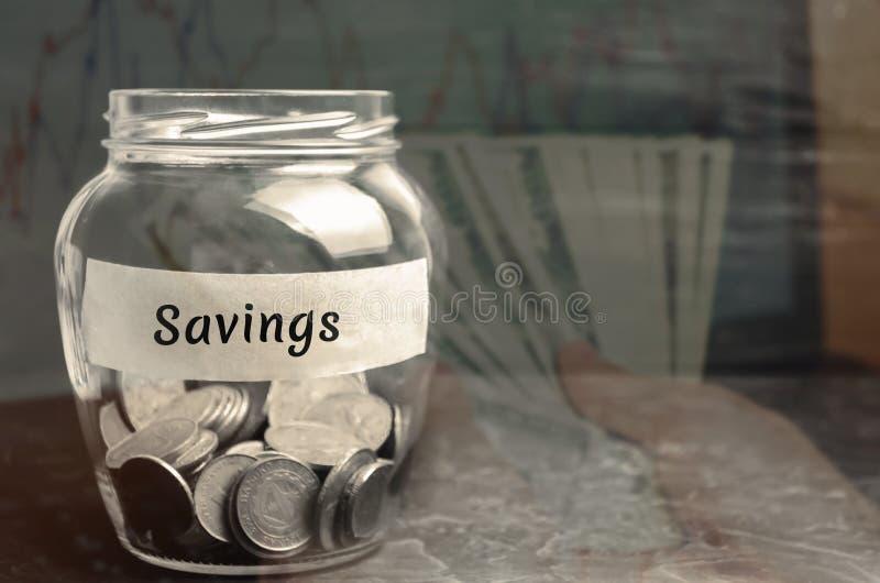 """Стеклянный опарник с монетками и надписью """"сбережения """" Концепция аккумулировать деньги в семейном бюджете Страхование семьи dist стоковые изображения"""