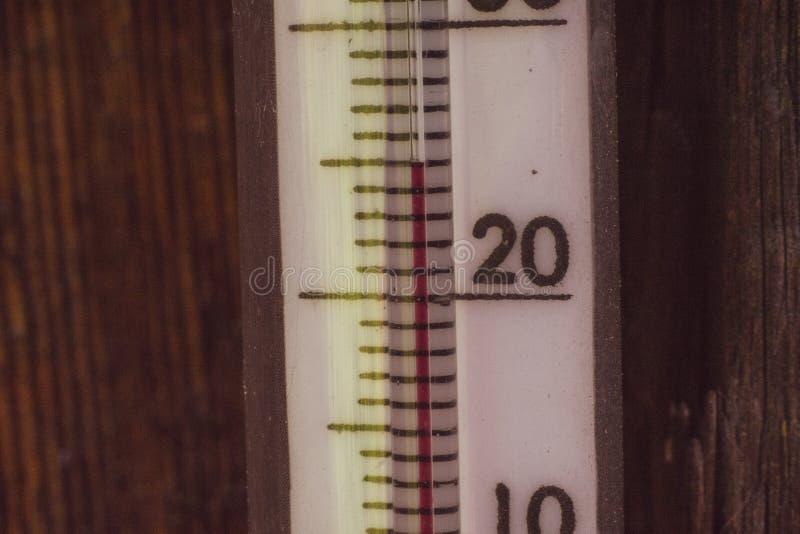 Стеклянный термометр показывает 25 градус цельсий Деревянная предпосылка стоковое фото