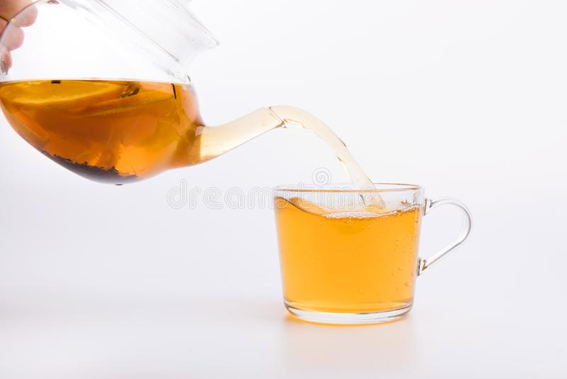 Стеклянный чайник лить зеленый чай в чашку изолированную на белизне стоковая фотография