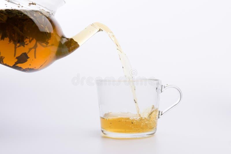 Стеклянный чайник лить зеленый чай в чашку изолированную на белой предпосылке стоковые изображения