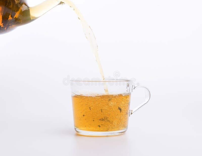 Стеклянный чайник лить зеленый чай в чашку изолированную на белой предпосылке стоковое изображение