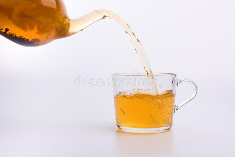 Стеклянный чайник лить зеленый чай в чашку изолированную на белой предпосылке стоковые изображения rf