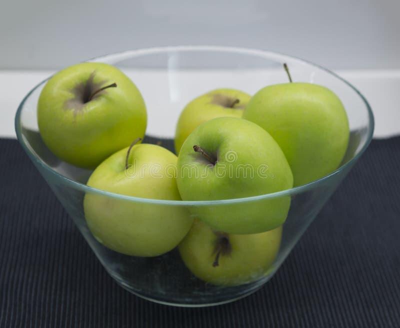 Стеклянный шар с зелеными яблоками кузнца бабушки на черной салфетке, белой стоковое изображение
