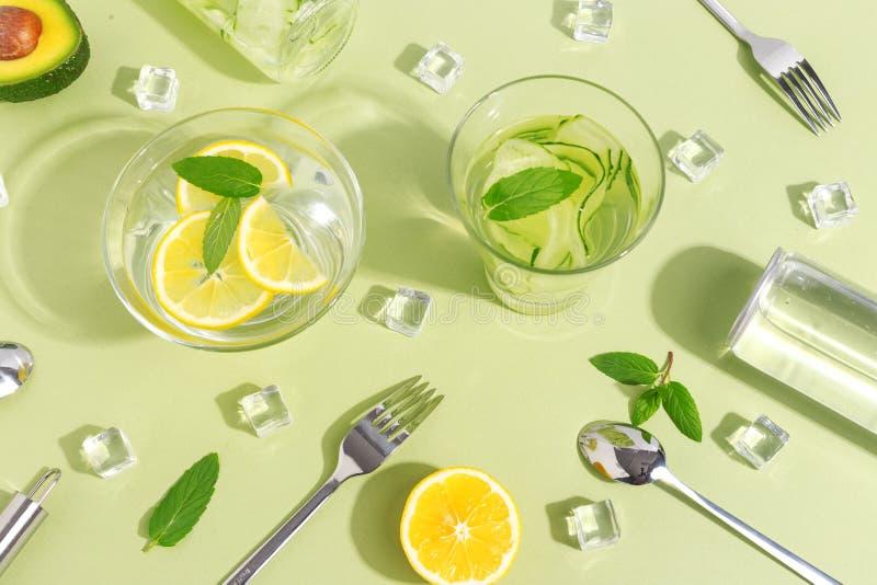Стеклянный beaker, бутылка воды огурца, плоды и столовый прибор на салатовой предпосылке Концепция Minimalistic творческая экземп стоковые изображения