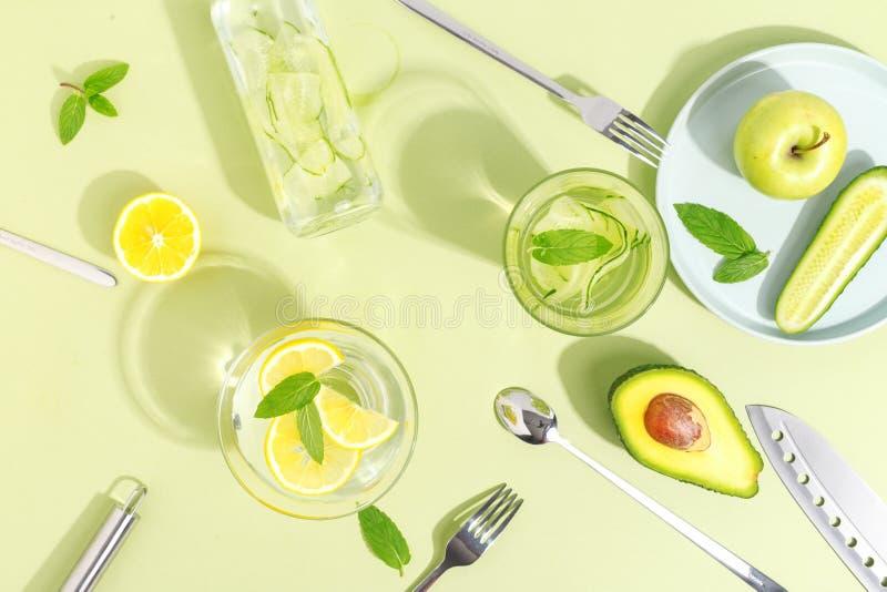 Стеклянный beaker, бутылка воды огурца, плоды и столовый прибор на салатовой предпосылке Концепция Minimalistic творческая экземп стоковые изображения rf