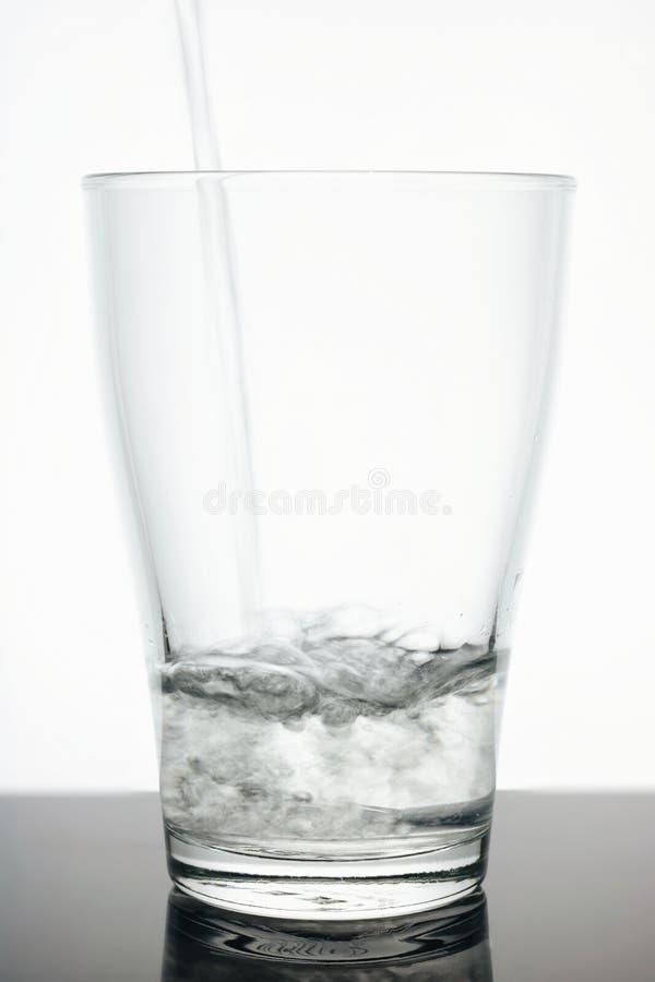 Стеклянный beaker в который вода пропускает Вода чиста - стекло прозрачно белизна предпосылки стеклянная Вода чисто экологичность стоковые изображения rf