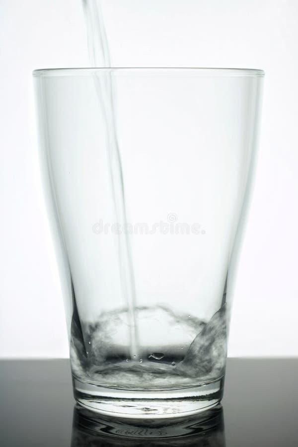 Стеклянный beaker в который вода пропускает Вода чиста - стекло прозрачно белизна предпосылки стеклянная Вода чисто экологичность стоковые фото