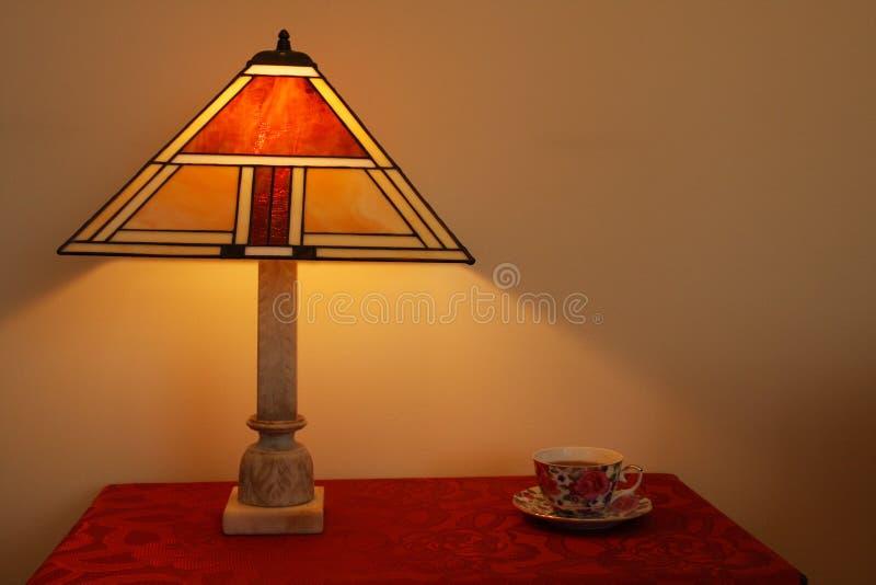 стеклянным таблица запятнанная светильником стоковое изображение rf
